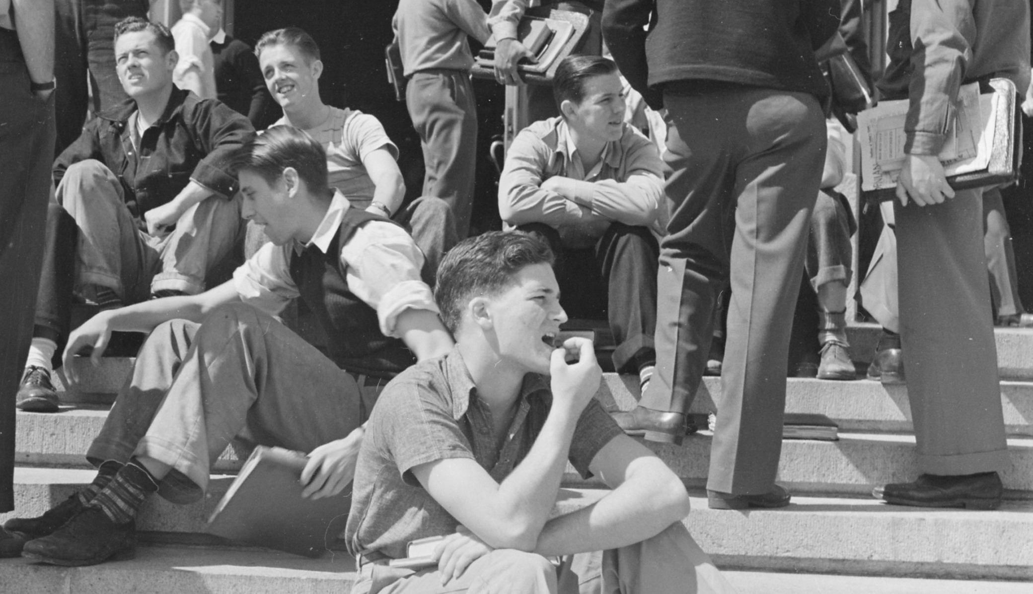 A black and white photo of male students sitting on the steps of Wheeler Hall on the University of California, Berkeley campus in 1940.
