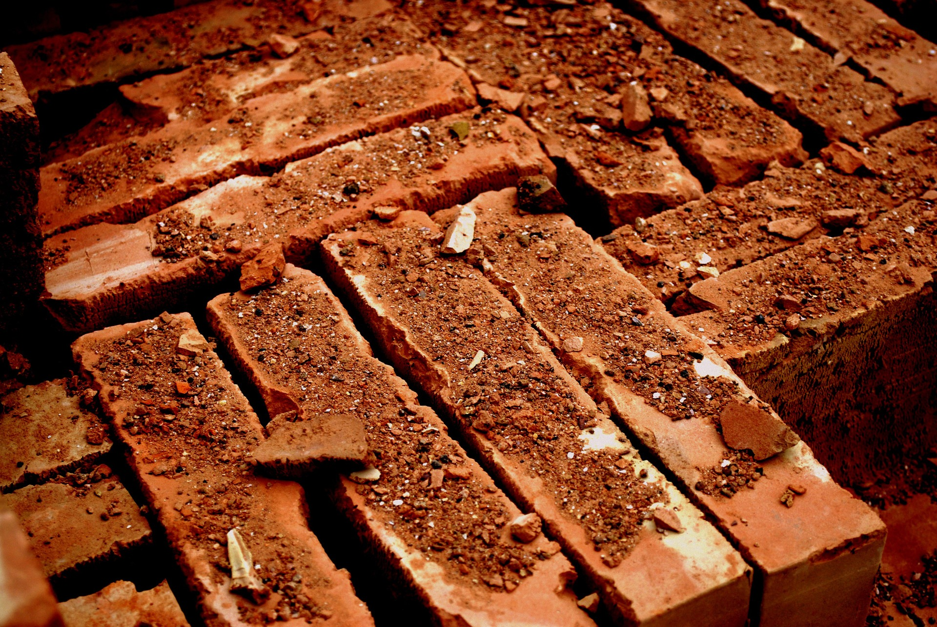 A pile of worn bricks covered in dust and chips of other bricks.