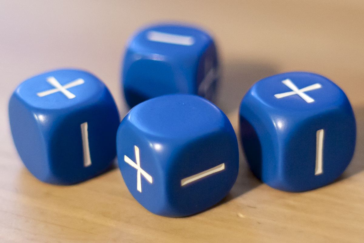A set of four blue Fate dice resting on top of a wooden table.