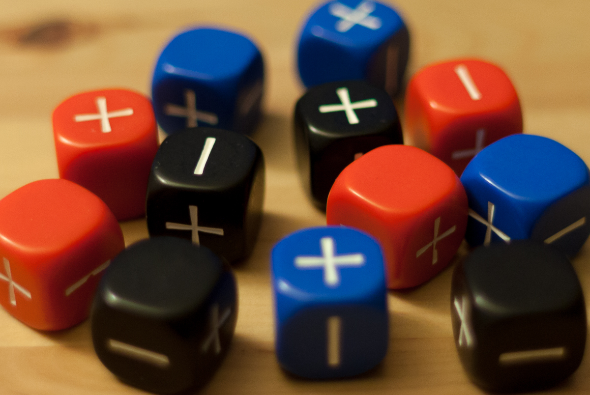 Three sets of four Fate dice, colored blue, red, and black, resting on top of a wooden table.