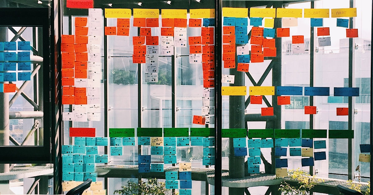 Colorful sticky notes arranged in a grid on the window of an office building.
