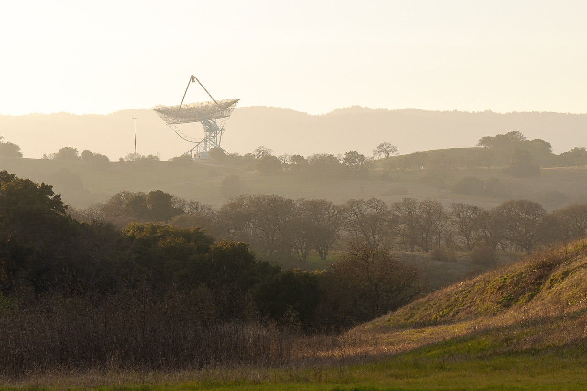 A landscape of the Stanford hills including the Stanford Dish shrouded in light fog. The sun is setting behind the dish making the sky appear bright white.