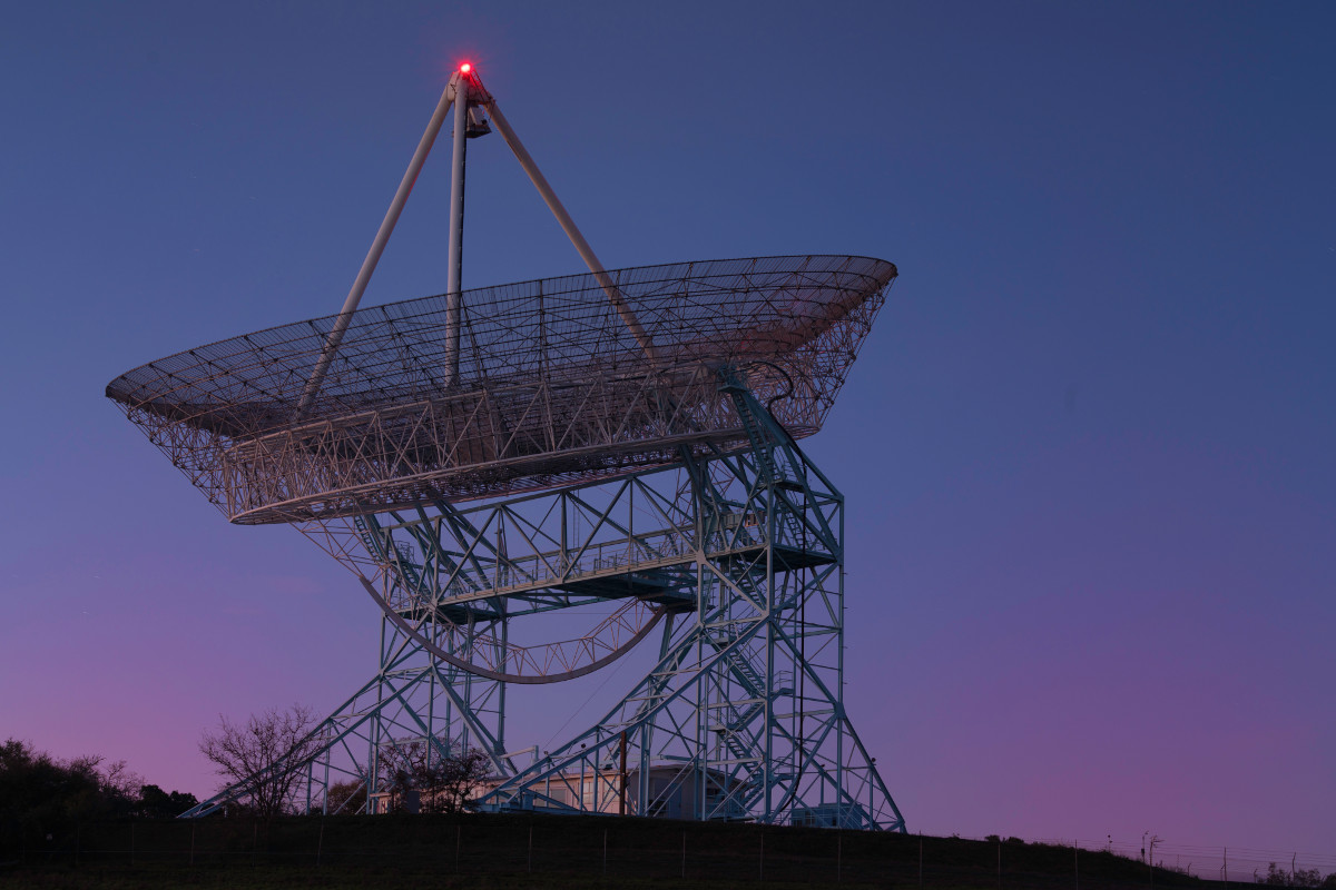 The Stanford Dish, a large radio telescope, in the early morning light. The sky is purple and blue, and the dish is a white metal-lattice structure glowing softly pink in the light. At the top of the dish is a red light.