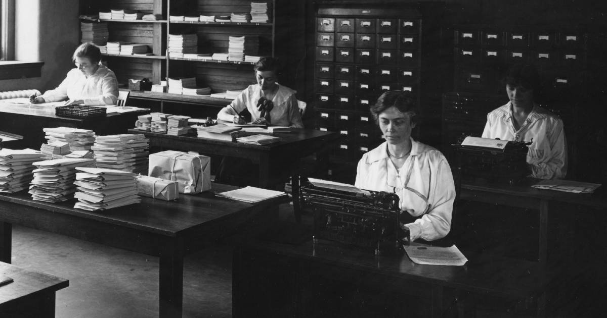 A black and white photo of four women sitting at desks with typewriters, stacks of papers, and card catalogs.