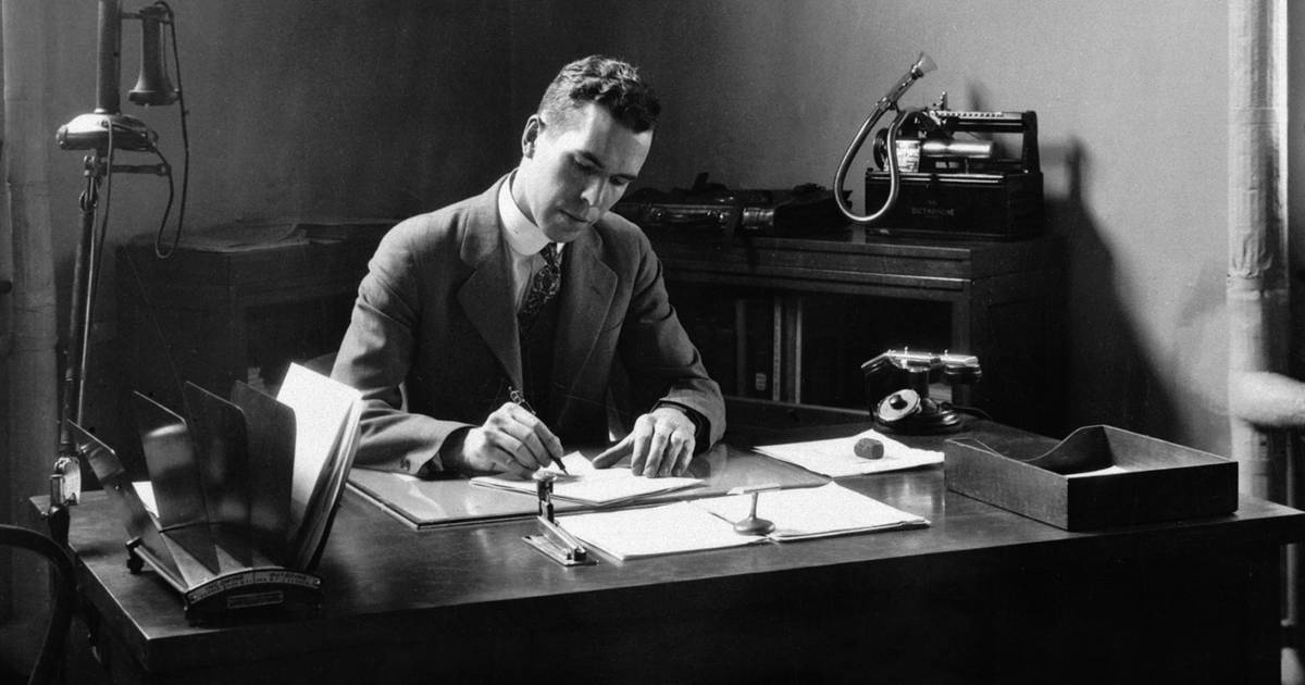 A black and white photo of Henry J.E. Reid, Directory of the Langley Aeronautics Laborator, in a suit writing while sitting at a desk.