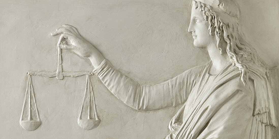 A relief showing a women holding up a set of balance scales.