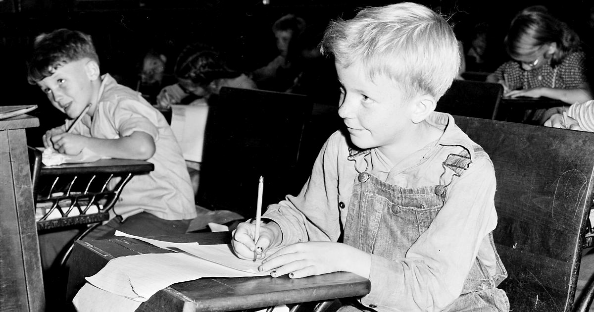 Black and white photo of a young boy at a school desk.