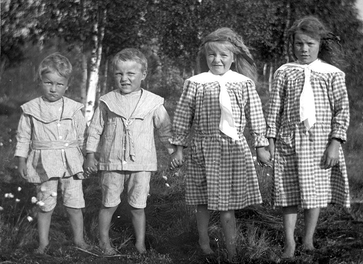 A photo of four Swedish children, two boys and two girls, taken sometime in the 1920s. The boys are wearing matching clothes, and the girls are wearing matching dresses.
