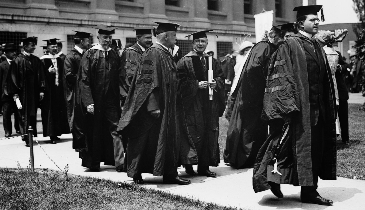 A black and white photo from the 1913 Columbia University Commencement featuring a group of men in doctoral gowns wearing mortarboards. Nobel Prize winner Alexis Carrel is amongst them.
