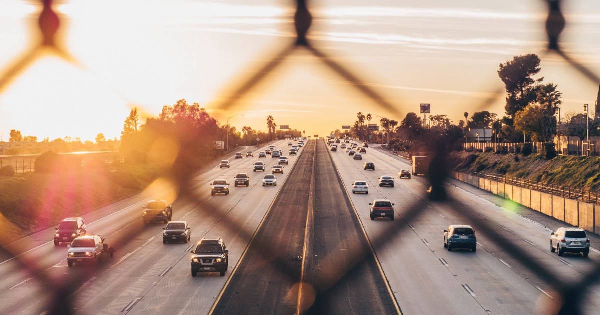 View of a freeway seen through a chain-link fence at sunset.
