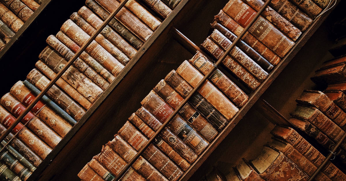 A picture of old books on shelves taken at an angle.