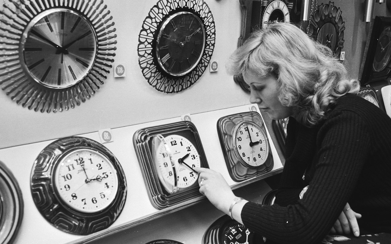 A blonde woman adjusts the time on a row of clocks at a store.