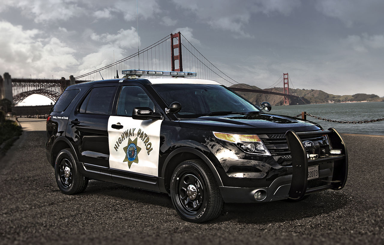 A sports utility vehicle belonging to the California Highway Patrol is parked in front of the Golden Gate Bridge.