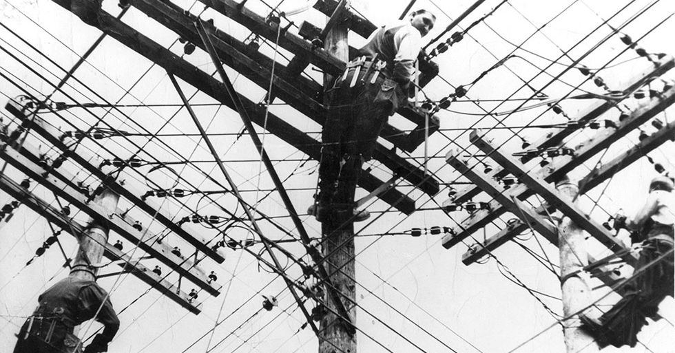 A black and white photo of three linesmen repairing a tangle of overhead wires.
